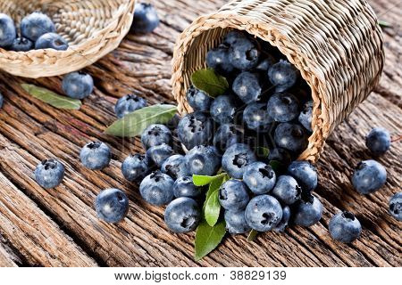 Blueberries have dropped from the basket on an old wooden table.