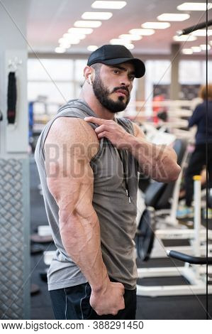 Strong Young Bearded Male Showing Big Triceps Muscle During Posing In Sport Gym After Hard Workout T