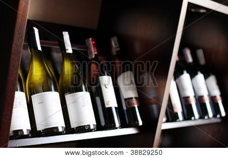 Wine bottles on a wooden shelf.