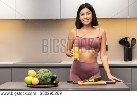 Healthy Diet. Cheerful Slim Japanese Woman Drinking Juice Cooking Dinner For Weight Loss Standing In