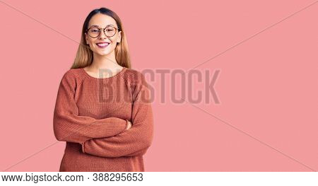 Beautiful young woman wearing casual clothes and glasses happy face smiling with crossed arms looking at the camera. positive person.