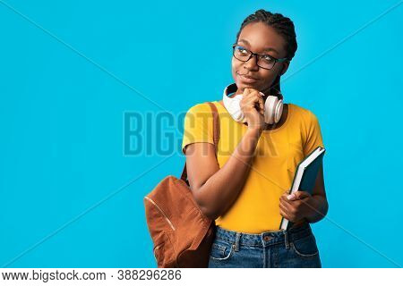 Let Me Think. Thoughtful African American Woman Student Thinking Holding Books Standing On Blue Stud
