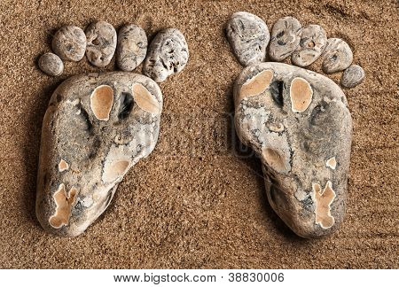 two trace feet made of a pebble stone on the sea sand desert , texture backdrop