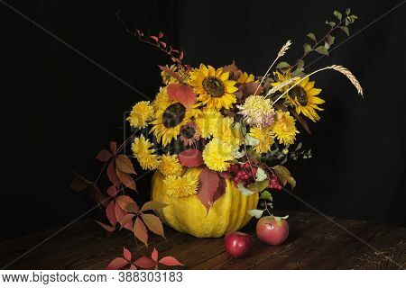Flower Arrangement With Sunflowers In A Pumpkin On A Wooden Table On A Black Background. Thanksgivin