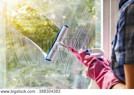 A Woman Clean A Window Pane With A Squeegee And Soap Suds. Cleaning With A Detergent. Hands In Pink