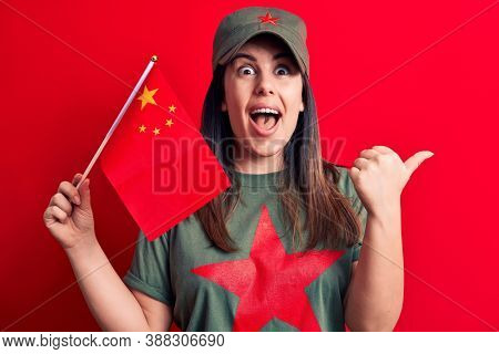 Beautiful patriotic woman wearing t-shirt with red star communist symbol holding china flag pointing thumb up to the side smiling happy with open mouth