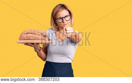 Young blonde woman holding wholemeal bread annoyed and frustrated shouting with anger, yelling crazy with anger and hand raised