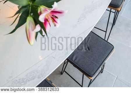 kitchen stool with cushion and out of focus lilly flowers