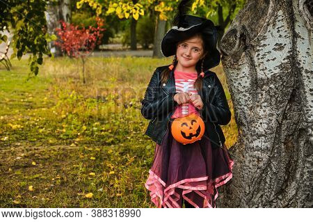 Little Girl In Witch Costume Playing In Autumn Park.