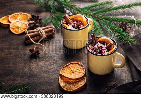 Christmas Mulled Wine With Cranberries, Orange And Spices In Mugs On Rustic Plywood Background. Trad