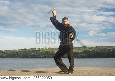 The Bearded Man In Black Kimono Is Practicing Ninja Style In Martial Arts With Two Nunchuks Outdoors