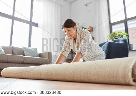 household, home improvement and interior concept - young woman unfolding carpet