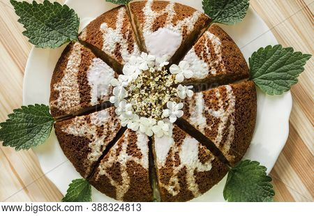 Sliced, Divided Sponge Pie Into Portion On A Wooden Background. Dark Cake, Drizzled With White Icing