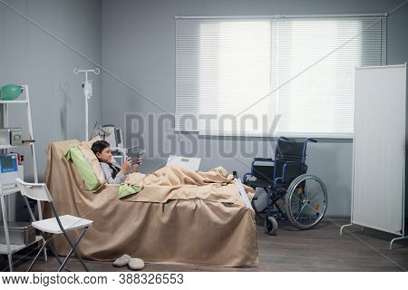 Hospital Medicine Tray With Patient Asleep In Background.