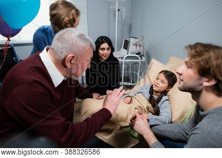 A Family Consoling The Little Girl During Their Visit At The Hospital.