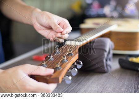 Acoustic Guitar Care, Craftsman Is Changing The Strings, Close Up.