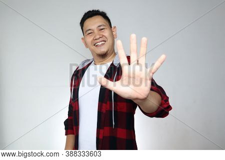 Portrait Of Attractive Young Asian Man Shows Hi Or High Five Gesture With His Fingers Over Grey Back