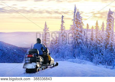 Man Standing On Snowy Mountain Near Snowmobile Enjoying View Winter Forest At Sunset. Concept Winter
