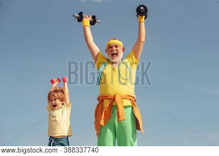 Age Is No Excuse To Slack On Your Health. Boy Is Doing Exercises To Develop Muscles. Father And Son