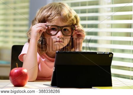 Child Boy In Glasses Using A Tablet And Study Online With Video Call Teacher At Home, Homeschooling,