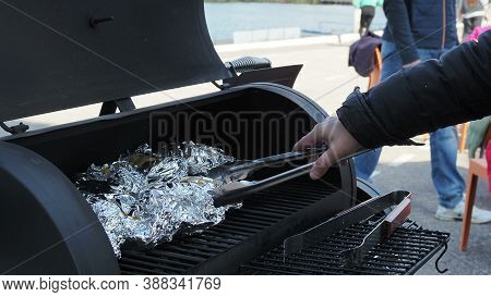 Home Cooking - Unwrapping Potato Being Baked Or Cooked On Gas Grill Wrapped In Aluminium Foil With S