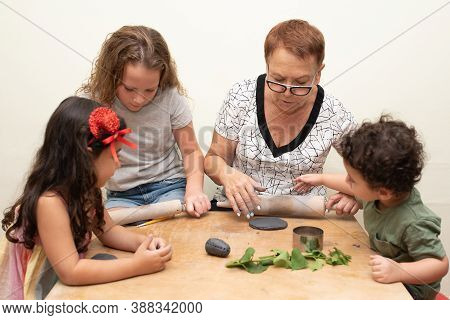 A Senior Woman Is Teaching A Little Kids How To Form With Clay. Grandmother Helping Little Grandchil