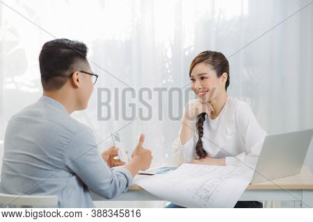 Young Asian Man At Real Estate Agent In Office With Famale Seller.