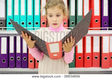 Surprised girl looks big folder and stands near to shelves with folders.
