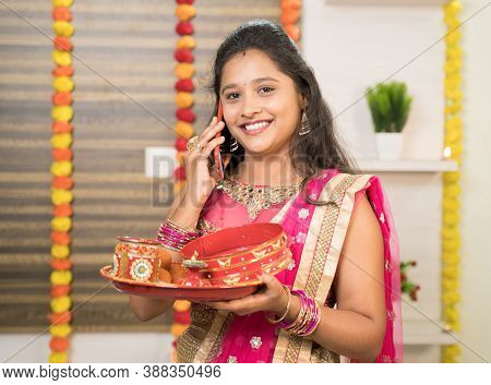Smiling Indian Woman In Traditional Dress Holding Karva Chauth Thali Or Plate While Busy In Talking