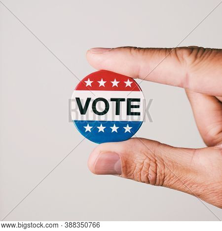 closeup of a young caucasian man with a vote badge for the United States election in his hand, on an off-white background