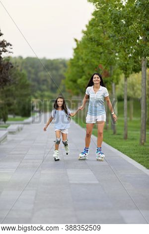 Young Mother And Her Cute Little Daughter Rollerskating In Summer Park. Family Concept