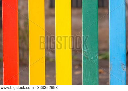Part Of Wooden, Rainbow Colorful Painted Fence On A Sunny Hot Summer Day In A City Park. Abstract Mu