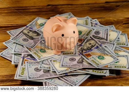 Pink Piggy Bank On A Heap Of American One Hundred Dollars Bills On A Wooden Desk