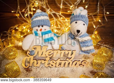 Toys On Shiny Garlands Background. Merry Christmas And Happy New Year. Wooden Text.