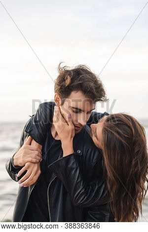Woman Touching Cheek And Embracing Boyfriend In Leather Jacket Near Sea