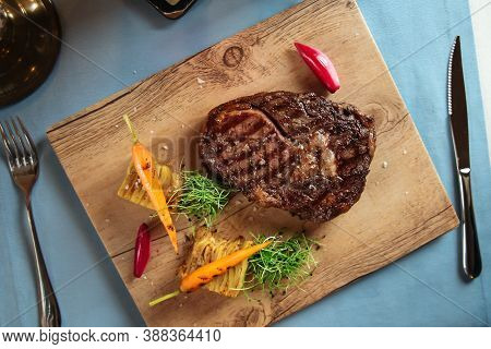 Top View On Grilled Beef Ribeye Steak With Potatoes On The Wooden Board