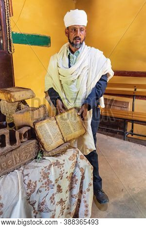 Yeha, Tigray Region, Ethiopia - April 28, 2019: Orthodox Priest Shows A Painted Holy Bible In Amhari