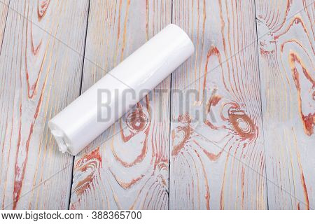 The Wooden Background Is Artificially Aged. On It Is A Roll Of Transparent Polyethylene Bags. Enviro