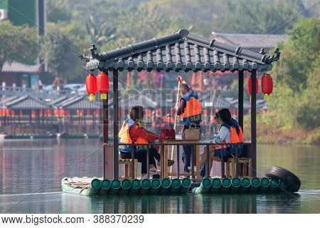 Yangshuo, Guilin, Guangxi Province, China - November 10, 2019: Tourists On A Bamboo Raft With Chines