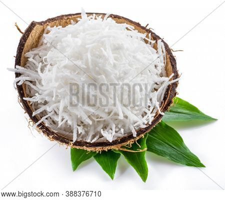 Shredded coconut flakes in the coconut shell isolated on white background.