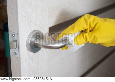 Coronavirus Covid-19 Woman Hand Wiping Doorknob With Antibacterial Disinfecting Wipe For Killing Cor