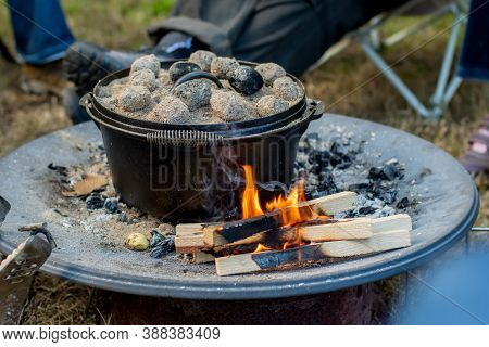 Dutch Oven Campfire Cooking With Coal Briquettes On Top, Camping Life.