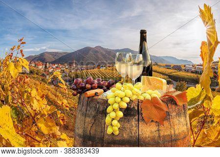 Bottle Of White Wine With Glasses Against Weissenkirchen Village With Autumn Vineyards In Wachau Val