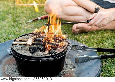 Dutch Oven Campfire Cooking With Coal Briquettes And Flame On Top, Camping Life.