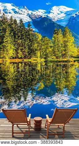 Concept of active and ecotourism. Fantastic sunset in the autumnal Alps. Stunning reflections of snowy peaks in the lake water. Mountain resort of Chamonix, the foot of Mont Blanc