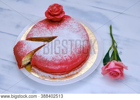 Red Cake Covered With Marzipan Or Mastic With A Cut Piece And Sprinkled With White Powdered Sugar, B