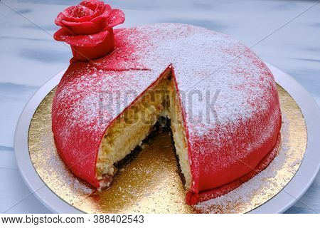 Red Cake Covered With Marzipan Or Mastic With A Cut Piece, Close-up, Background