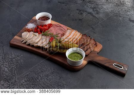 Assortment Of Delicious Deli Meats, Pickled Cucumbers, Sun-dried Tomatoes And Two Sauces