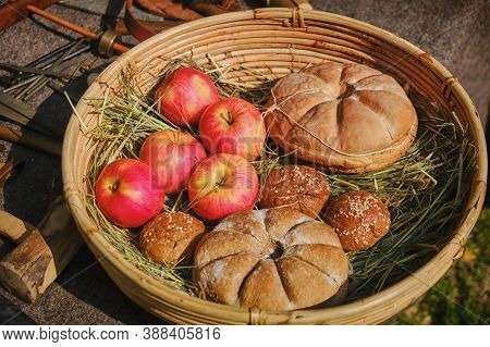 Bread Baked On Retro Technology With Apples In The Basket. Reconstruction Of Cooking In The Ancient
