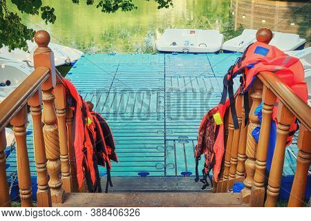 The Dock With Paddle Boats In The Pond. Entrance To The Boat Station With Life Jackets., Background